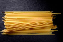 Uncooked spaghetti noodles. Uncooked spaghetti lie on a diagonal direction Royalty Free Stock Photos
