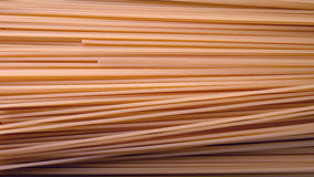 Uncooked spaghetti noodles. Uncooked spaghetti lie on a diagonal direction Stock Image