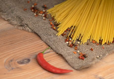Uncooked Spaghetti with spices on dark table. Royalty Free Stock Image