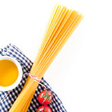 Uncooked spaghetti with tomatoes and olive oil. Lying on a fresh blue and white checked napkin on a white background with copyspace, overhead view Royalty Free Stock Image