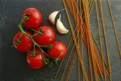 Uncooked spaghetti z pomidorami i garluc Fotografia Stock
