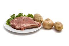Uncooked steak with potatoes. Uncooked steak, potatoes and onion on white background Stock Photography
