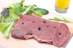 Uncooked steak with salad Royalty Free Stock Images