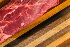 Uncooked steak sitting on wooden cutting board