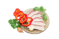 Uncooked streaky bacon, bell pepper, sprigs parsley and coriande. Uncooked slices of streaky pork belly bacon on glass saucer, sliced bell pepper, sprigs parsley stock photography
