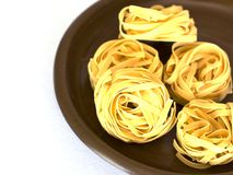 Uncooked tagliatelle on a ceramic plate. Isolated Royalty Free Stock Images