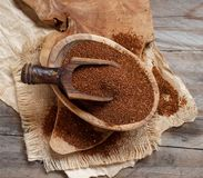 Uncooked teff grain in a bowl. With a spoon top view Royalty Free Stock Image