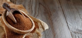 Uncooked teff grain in a bowl. With a spoon close up Royalty Free Stock Image