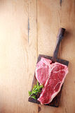 Uncooked tender porterhouse or t-bone steak. On an old wooden board with a sprig of fresh rosemary waiting to be cooked, view from above on wood with copyspace Royalty Free Stock Photos