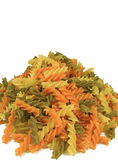 Uncooked Three-color Fusilli Pasta Piled-up on White Background, Vertical Front View Photo with Free Space for Text Stock Image