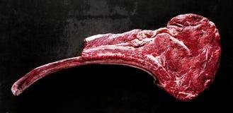 Uncooked tomahawk steak on black