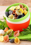 Uncooked tricolor pasta in bowl Stock Photos