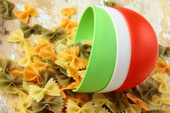 Uncooked tricolor pasta in cups Royalty Free Stock Photos