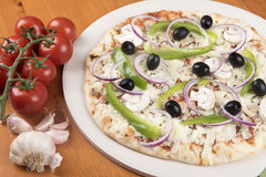 Uncooked vegetarian pizza with olives, peppers, onion, mushrooms and garlic. On a wooden background stock photo