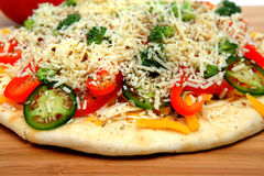 Uncooked Vegtable Pizza For One. A veggie pizza ready to go into the oven topped with sharp cheddar and asiago cheese, fresh tomatoes, red bell pepper, mild Stock Image