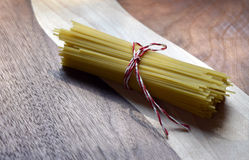 Uncooked Vermicelli noodles tied with string on a wood cutting board Royalty Free Stock Images