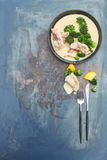 Uncooked white fish with bechamel sauce and broccoli. A bowl of uncooked white fish with bechamel sauce and broccoli  in a grunge blue background Royalty Free Stock Images