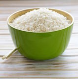 Uncooked white rice in a green bowl Stock Photo
