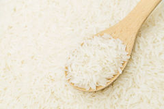 Uncooked white rice on wooden teaspoon Stock Photo