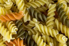 Uncooked Yellow and Green Fusilli Pasta. Uncooked green and yellow fusilli pasta close up royalty free stock photo