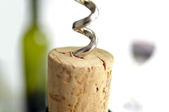 Uncork it. Corkscrew and cork closeup with bottle in background Royalty Free Stock Photography