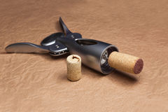 Uncork a bottle of wine. On brown background Royalty Free Stock Photo