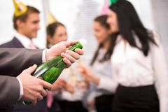 Uncorking bottle. Image of male hands holding bottle of champagne and uncorking it Stock Photos