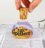 Uncorking tax repellent. Fingers lifting the cork from a bottle of tax repellent, letting the smoky potion seep onto a 1040 tax form Stock Image