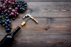 Uncorking the wine bottle. Bottle, corkscrew and bunches of grapes on wooden background top view copyspace Royalty Free Stock Image