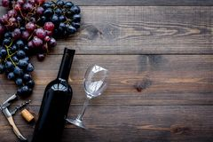 Uncorking the wine bottle. Bottle, corkscrew and bunches of grapes on wooden background top view copyspace Royalty Free Stock Photo