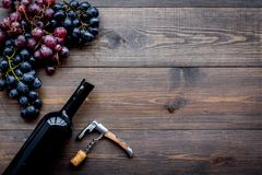 Uncorking the wine bottle. Bottle, corkscrew and bunches of grapes on wooden background top view copyspace. Uncorking the wine bottle. Bottle, corkscrew and Royalty Free Stock Photography