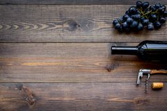 Uncorking the wine bottle. Bottle, corkscrew and bunches of grapes on wooden background top view copyspace Stock Photos