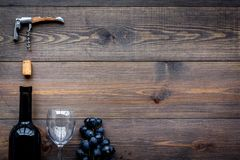 Uncorking the wine bottle. Bottle, corkscrew and bunches of grapes on wooden background top view copyspace Stock Images