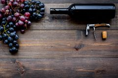 Uncorking the wine bottle. Bottle, corkscrew and bunches of grapes on wooden background top view copyspace Stock Image