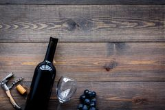Uncorking the wine bottle. Bottle, corkscrew and bunches of grapes on wooden background top view copyspace Stock Photography