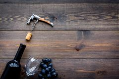Uncorking the wine bottle. Bottle, corkscrew and bunches of grapes on wooden background top view copyspace Royalty Free Stock Photography
