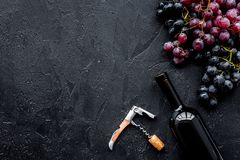 Uncorking the wine bottle. Bottle, corkscrew and bunches of red and black grapes on black background top view copyspace Royalty Free Stock Image