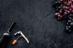 Uncorking the wine bottle. Bottle, corkscrew and bunches of red and black grapes on black background top view copyspace Royalty Free Stock Photo