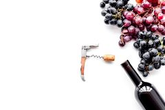 Uncorking the wine bottle. Bottle, corkscrew and bunches of red and black grapes on white background top view copyspace Stock Photography