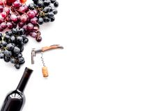 Uncorking the wine bottle. Bottle, corkscrew and bunches of red and black grapes on white background top view copyspace. Uncorking the wine bottle. Bottle Royalty Free Stock Photography