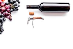 Uncorking the wine bottle. Bottle, corkscrew and bunches of red and black grapes on white background top view copyspace Stock Image