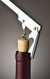 Uncorking Wine Bottle. Closeup of a modern metal cork screw pulling the cork from a wine bottle Stock Photography