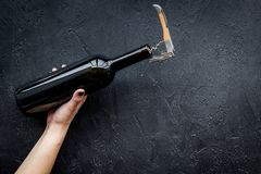 Uncorking the wine bottle. Hand hold bottle with corkscrew on black background top view copyspace Stock Images
