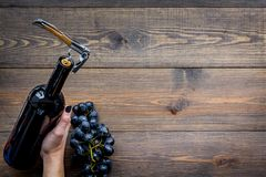 Uncorking the wine bottle. Hand hold bottle with corkscrew on wooden background top view copyspace Royalty Free Stock Photo