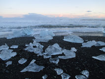 Uncountable icebergs on the black sand beach against sunset sky, Iceland Royalty Free Stock Photos
