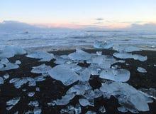 Uncountable roztapiające góry lodowa na czarnym piasku wyrzucać na brzeg pod zmierzchu niebem, Iceland Obraz Royalty Free