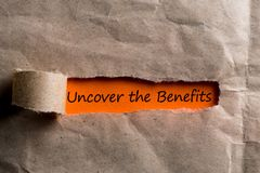 Uncover The Benefits message in letter or note, appearing behind ripped brown paper of envelope.  Stock Images