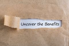 Uncover The Benefits text on brown envelope. Word Uncover The Benefits on torn paper. Concept Image.  Stock Photography