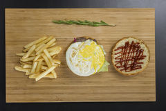Uncovered tasty burger with fried eggs and potato`s on the table Royalty Free Stock Images