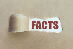 Uncovering the facts. Torn brown paper revealing the word facts Royalty Free Stock Image